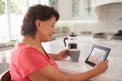 在家看老照片的资深西班牙妇女 免版税库存照片