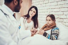 在家看见患者的印度医生 医生采取温度有怀孕的母亲的女孩 免版税库存照片
