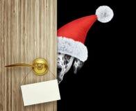 在家看门入口与空的卡片的红色圣诞节圣诞老人帽子的达尔马希亚狗 查出在黑色 免版税库存图片