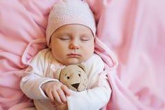 在家睡觉与在桃红色软的床上的玩具熊玩具的逗人喜爱的婴孩 免版税库存照片