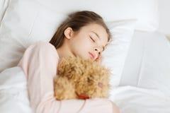 在家睡觉与玩具熊玩具的女孩在床上 免版税库存照片