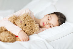 在家睡觉与玩具熊玩具的女孩在床上 免版税图库摄影