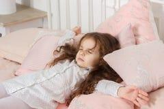 在家睡觉在一张桃红色床和观看的梦想上的小孩女孩 图库摄影