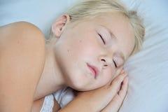 在家睡觉在她的床上的逗人喜爱的小女孩 库存图片