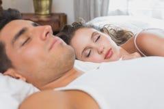 在家睡觉在床上的夫妇 免版税库存图片