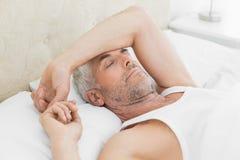 在家睡觉在床上的成熟人 免版税库存照片