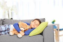 在家睡觉在有玩具熊的沙发的小孩 免版税库存图片