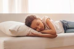 在家睡觉在沙发的小非裔美国人的女孩 免版税库存照片