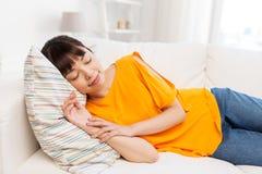 在家睡觉在沙发的年轻亚裔妇女 免版税库存图片