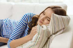 在家睡觉在沙发的微笑的十几岁的女孩 免版税库存照片