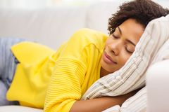 在家睡觉在沙发的非洲少妇 库存照片