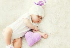 在家睡觉在白色床上的逗人喜爱的婴孩与被编织的枕头心脏 库存照片