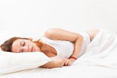 在家睡觉在白色枕头的秀丽红发女孩在床上 免版税图库摄影