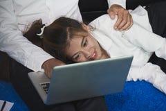 在家研究一台膝上型计算机的年轻商人有他的年轻wif的 免版税库存图片