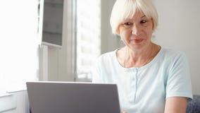 在家研究便携式计算机的年长资深白肤金发的妇女 愉快知道的好的消息激动和 股票视频