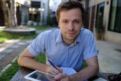 在家研究便携式计算机的微笑的人 免版税图库摄影