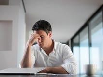 在家研究便携式计算机的沮丧的年轻商人 免版税库存图片
