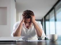 在家研究便携式计算机的沮丧的年轻商人 免版税图库摄影