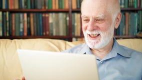 在家研究便携式计算机的英俊的年长老人 愉快知道的好的消息激动和 股票录像