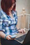 在家研究她的便携式计算机的年轻学生坐她的床 免版税库存照片