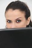 在家研究她的膝上型计算机的可爱的少妇 免版税库存图片