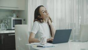 在家研究手提电脑的疲乏的妇女 接触脖子的被注重的妇女 股票录像