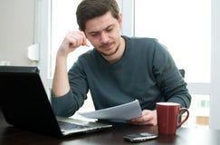 在家研究膝上型计算机的一个人的纵向 免版税库存照片