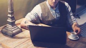 在家研究膝上型计算机的典雅的被刺字的人特写镜头,当坐在木桌上时 使用现代计算机为 免版税库存图片