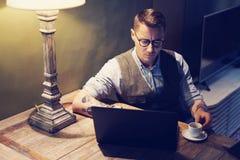 在家研究膝上型计算机的典雅的被刺字的人,当坐在木桌上时 使用新的研究的现代计算机 库存图片