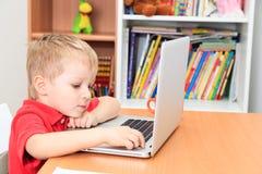 在家研究膝上型计算机的小男孩 免版税图库摄影
