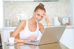 在家研究膝上型计算机的微笑的妇女 免版税库存图片