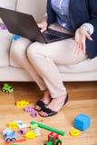 在家研究膝上型计算机的母亲 免版税图库摄影