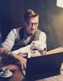 在家研究膝上型计算机的镜片的微笑的被刺字的人,当坐在与睡觉逗人喜爱的狗的木桌上时 图库摄影