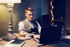 在家研究膝上型计算机的镜片的沉思被刺字的人,当坐在木桌上时 使用现代计算机为 库存照片