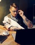 在家研究膝上型计算机的镜片的英俊的被刺字的人,当在与逗人喜爱的狗的木桌上坐他的时 库存图片