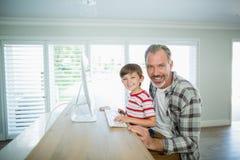 在家研究计算机的微笑的父亲和儿子 库存照片