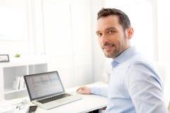 在家研究他的膝上型计算机的年轻商人 免版税库存图片