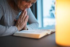 在家祈祷一名资深的妇女 库存图片