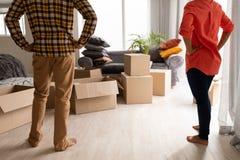 在家站立与在臀部的手一起的夫妇在客厅 免版税库存图片
