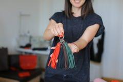 在家站立与皮革手工制造小装饰品工作室的女孩 免版税库存照片