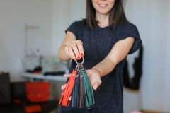 在家站立与皮革手工制造小装饰品工作室的妇女 免版税库存图片