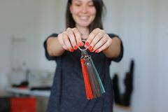 在家站立与皮革手工制造小装饰品工作室的微笑的女性 免版税库存照片