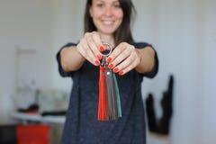 在家站立与皮革手工制造小装饰品工作室的愉快的女性 库存照片