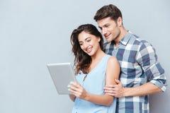 在家站立和使用数字式片剂的夫妇 图库摄影