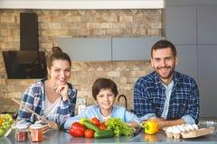 在家站立在厨房里的家庭一起看照相机快乐准备好烹调 免版税库存照片