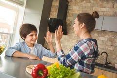 在家站立在厨房里的家庭一起给高五笑的快乐的侧视图 免版税库存照片