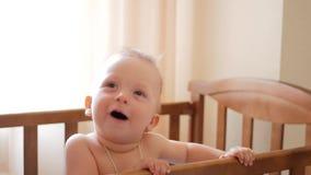 在家站立在婴孩小儿床的婴孩` s 学会的小男孩站立在他的小儿床 股票录像