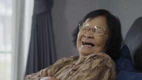 在家笑在客厅的资深妇女的慢镜头 股票视频