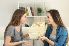 在家给礼物的愉快的朋友 免版税库存图片