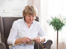 在家编织在轮幅的一名中年妇女的画象 图库摄影